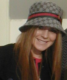 A red-haired Caucasian female wearing a black coat and a hat.