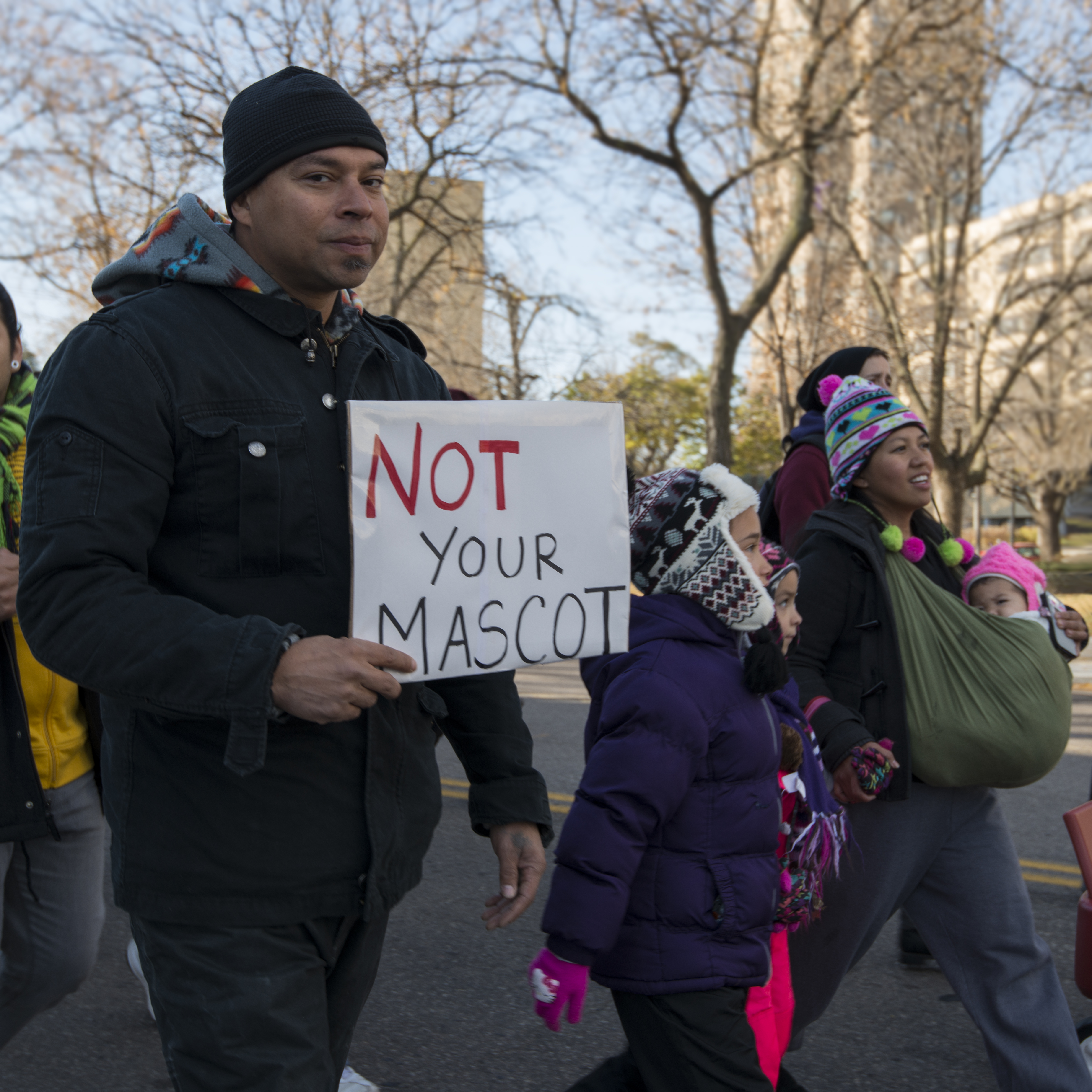 """Protestor marching in street holding sign that reads """"Not Your Mascot."""""""