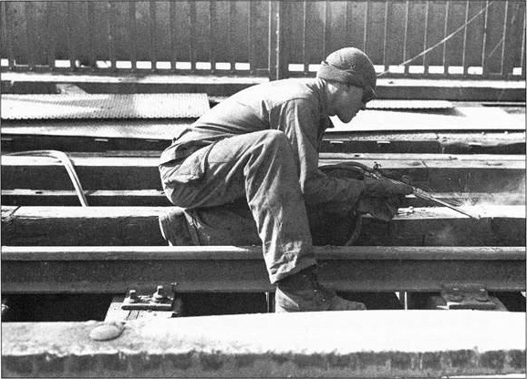 A welder from the 1058th Bridge Construction and Repair Group repairs the Bridge after it was captured