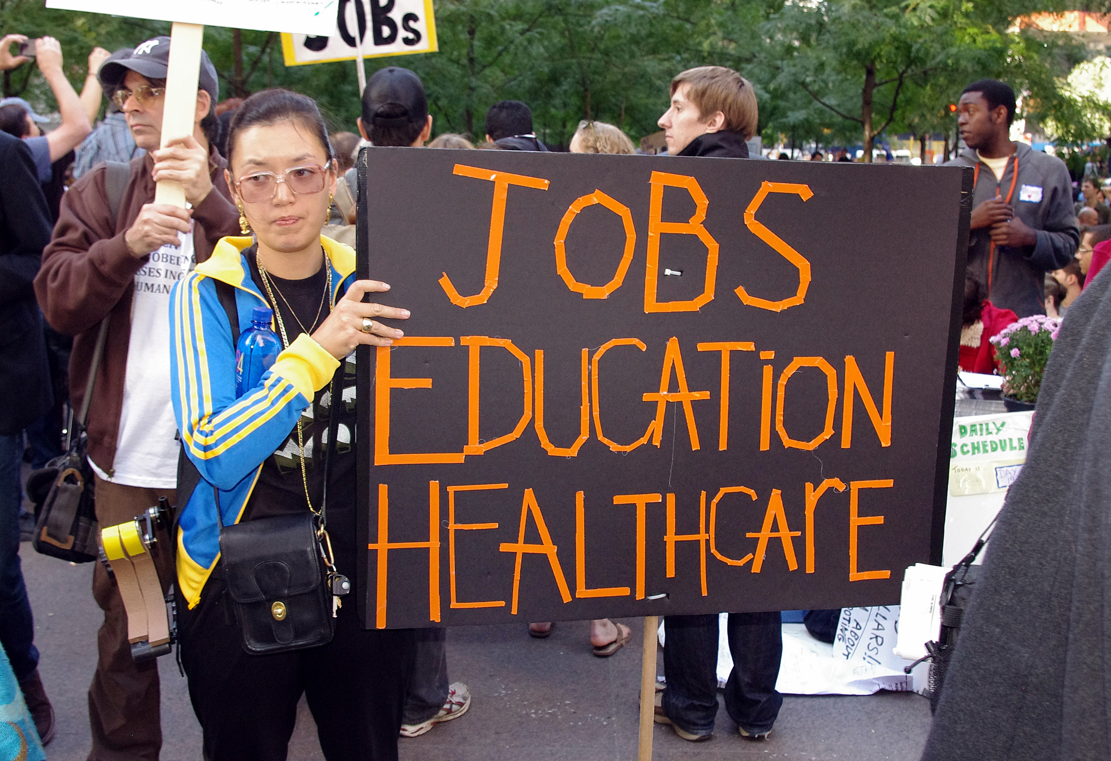 """A woman stands in the foreground holding a black and orange protest sign that reads """"Jobs, Education, Healthcare""""."""