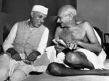 Two smiling men in robes sitting on the ground with bodies facing the viewer and with heads turned toward each other. The younger wears a white Nehru cap; the elder is bald and wears glasses. A half-dozen other people are in the background.