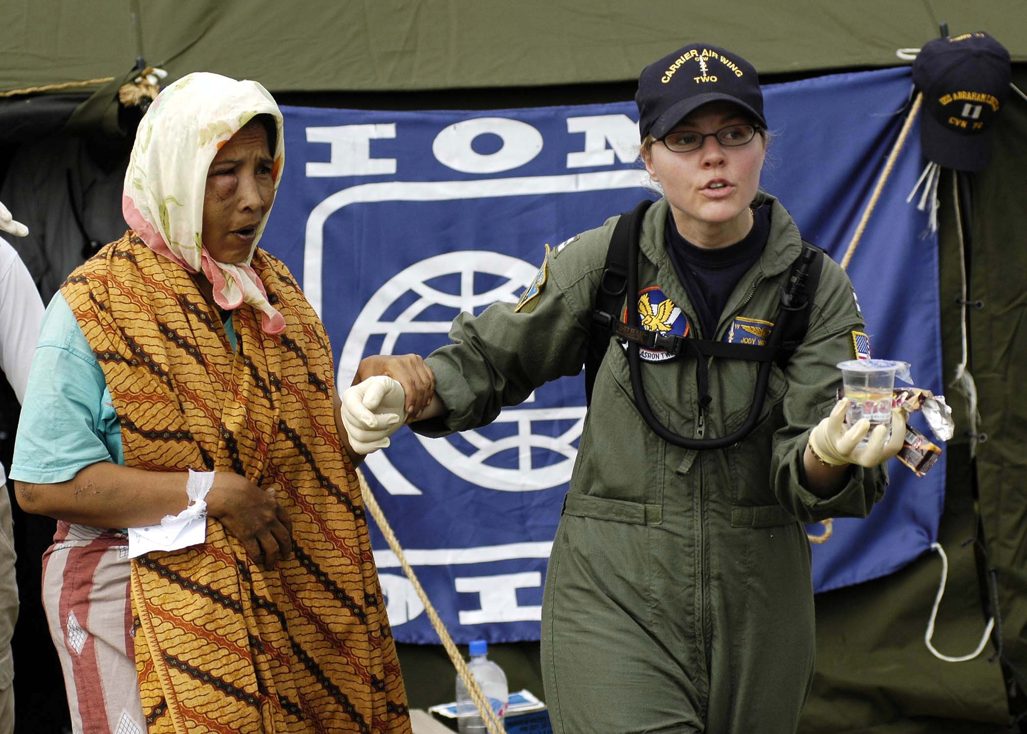 https://upload.wikimedia.org/wikipedia/commons/9/9e/US_Navy_050103-N-4166B-237_Lt._Jody_Weinstein_helps_an_injured_Indonesian_woman_into_a_medical_evacuation_vehicle_after_she_was_transported_from_a_coastal_village_on_the_island_of_Sumatra%2C_Indonesia.jpg