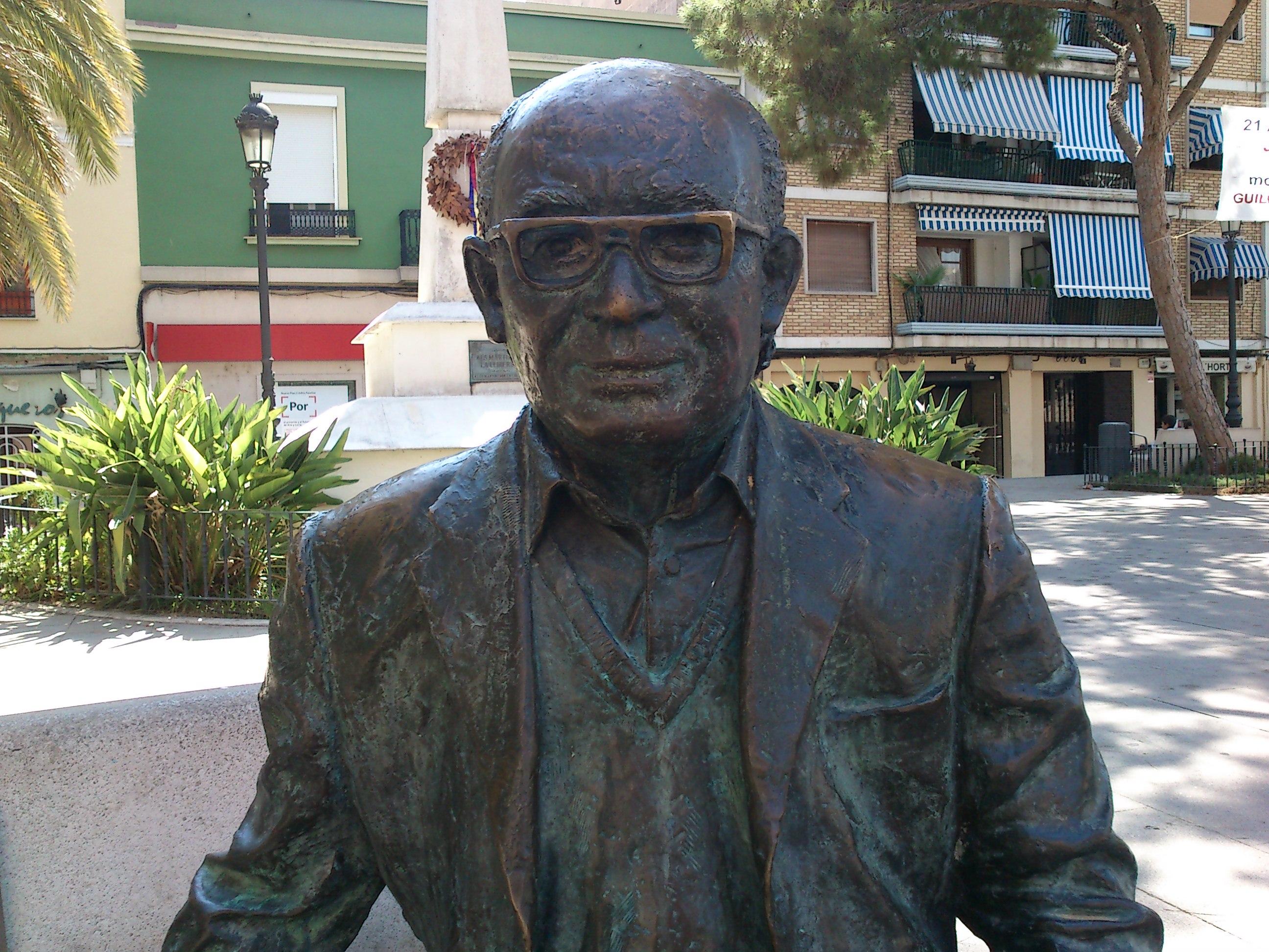 Estatua en bronce del autor sentado en un banco de la plaza Emilio Castelar de Burjasot
