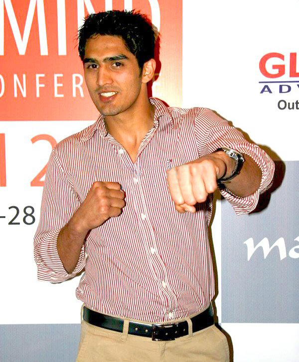 Picture of an young Indian male up to the waist. He has sharp features, short cropped black hair and is clad in a pink striped shirt and khaki pants with a black belt. The man appears to look a little to the right of the camera, smiling and making a gesture with his left hand as if he is punching.
