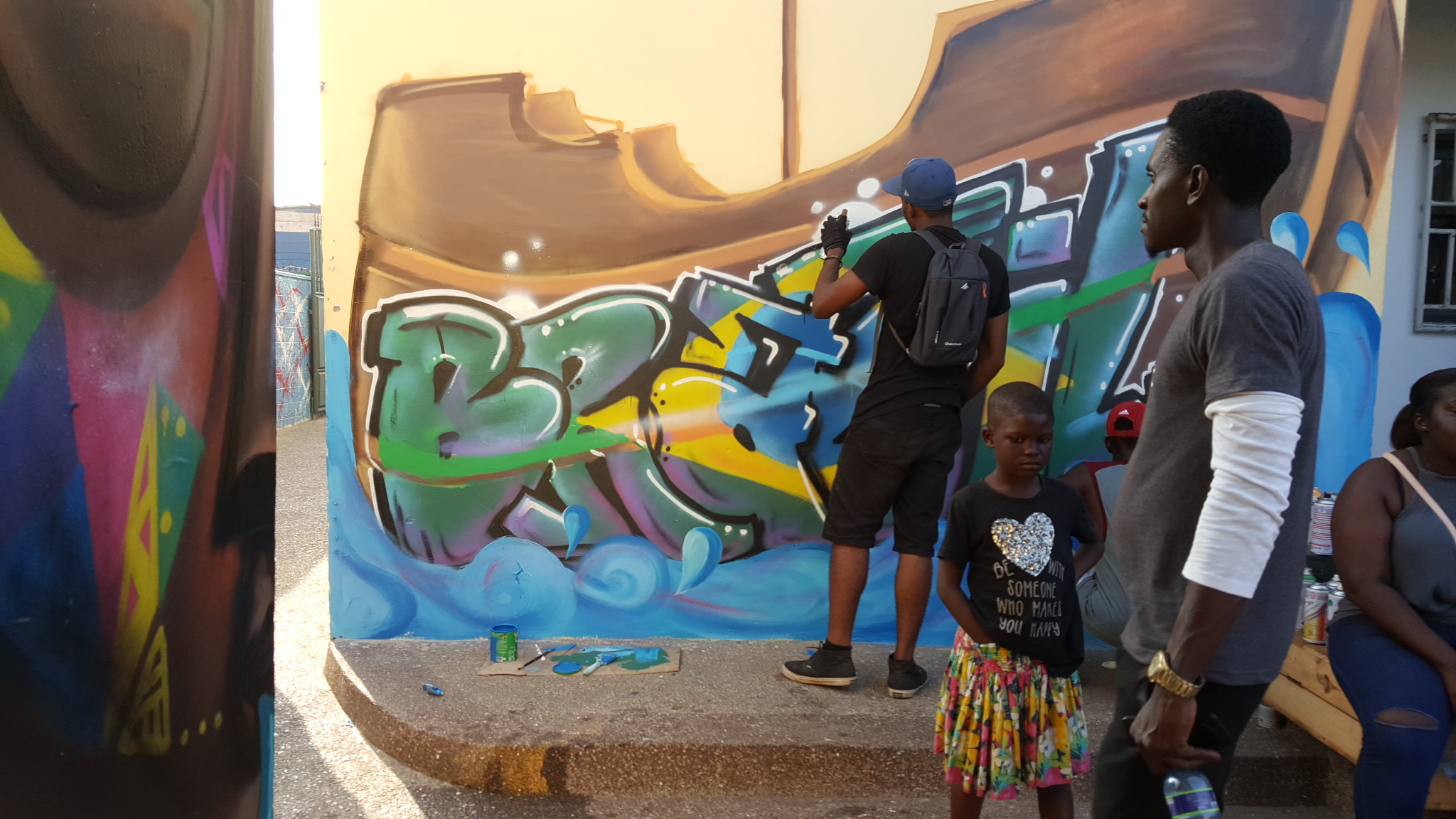 A graffiti artist spraying at Brazil House in Accra.jpg