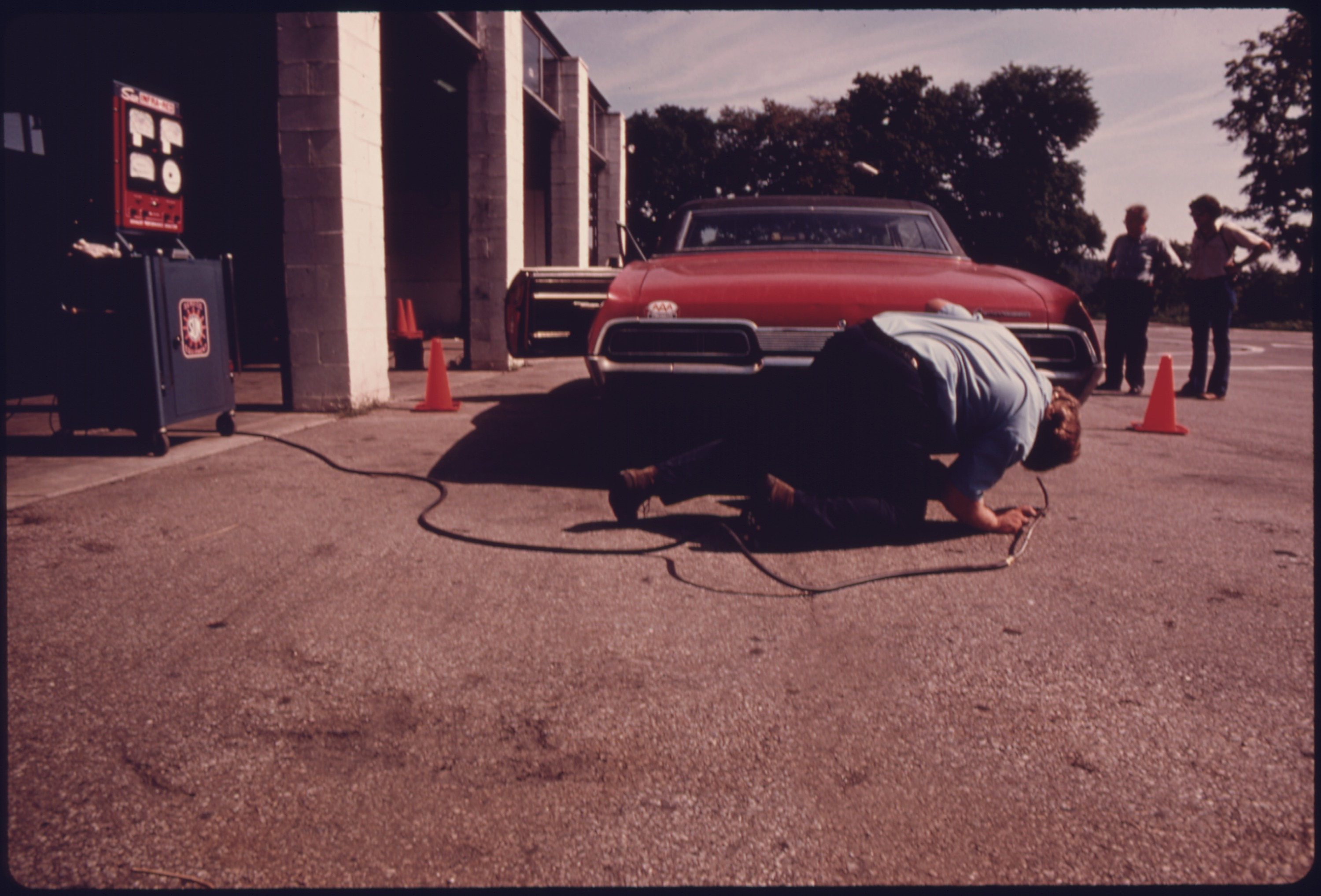Employee at the hamilton county auto emission inspection station at newtown%2c ohio. checks the exhaust system for a...   nara   557833