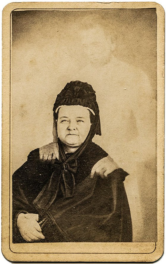 "Mary Todd Lincoln with the ""ghost"" of her husband, in an image taken by spirit photographer William H. Mumler. Mumler's photos are now considered hoaxes."