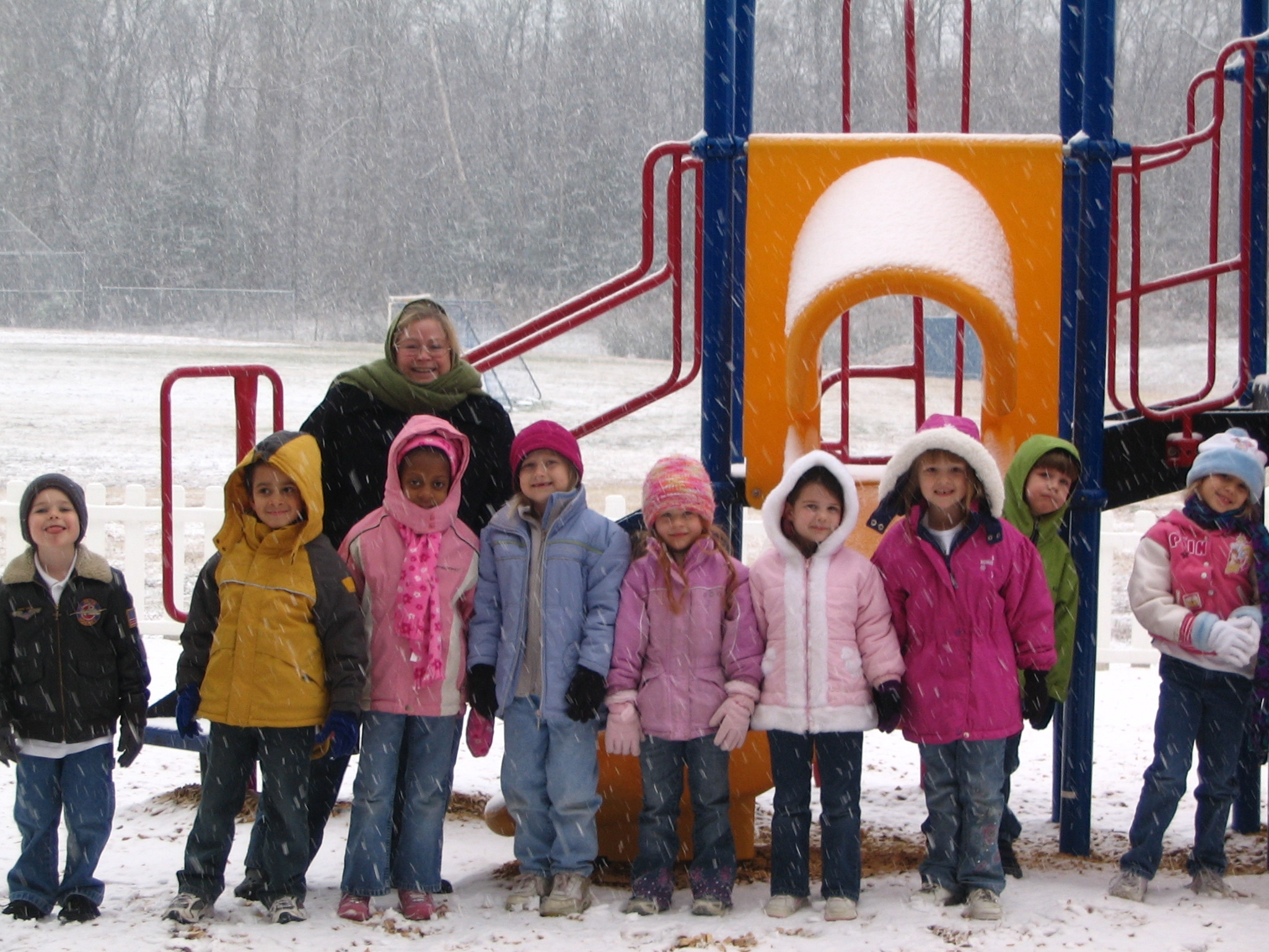 Young children and teacher posing for a picture in front of a play structure while it is snowing