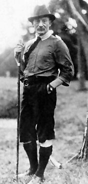black and white photograph of a man standing outdoors, facing the camera