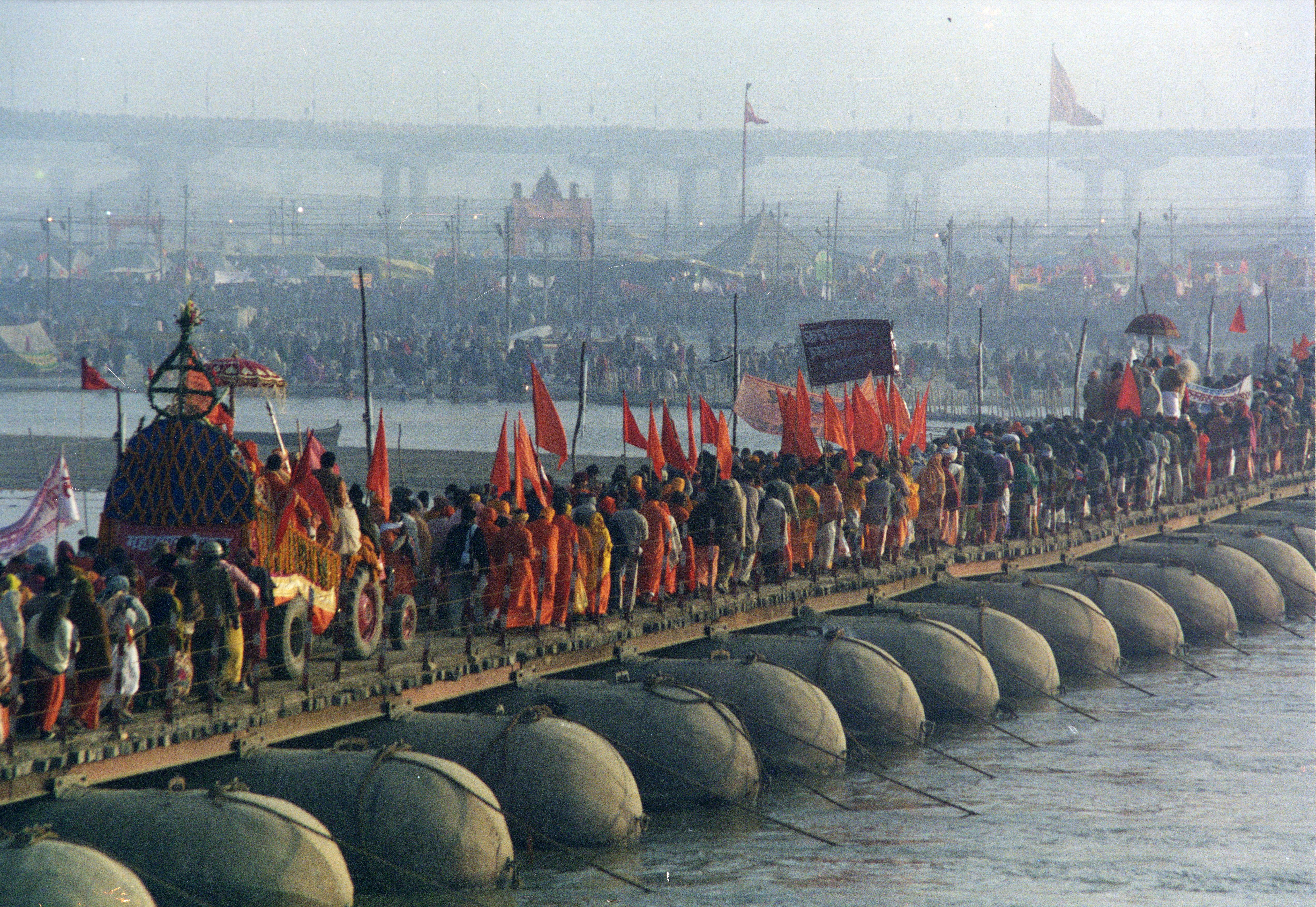 A procession of Akharas marching over a makeshift bridge over the Ganges river, Kumbh Mela at Allahabad, 2001