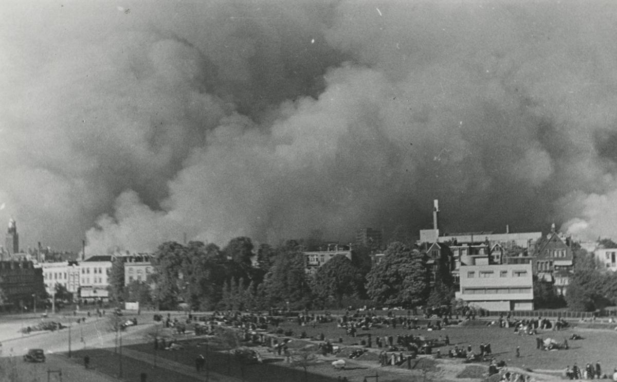 Mensen verzamelen zich op het Land van Hoboken terwijl de stad brandt