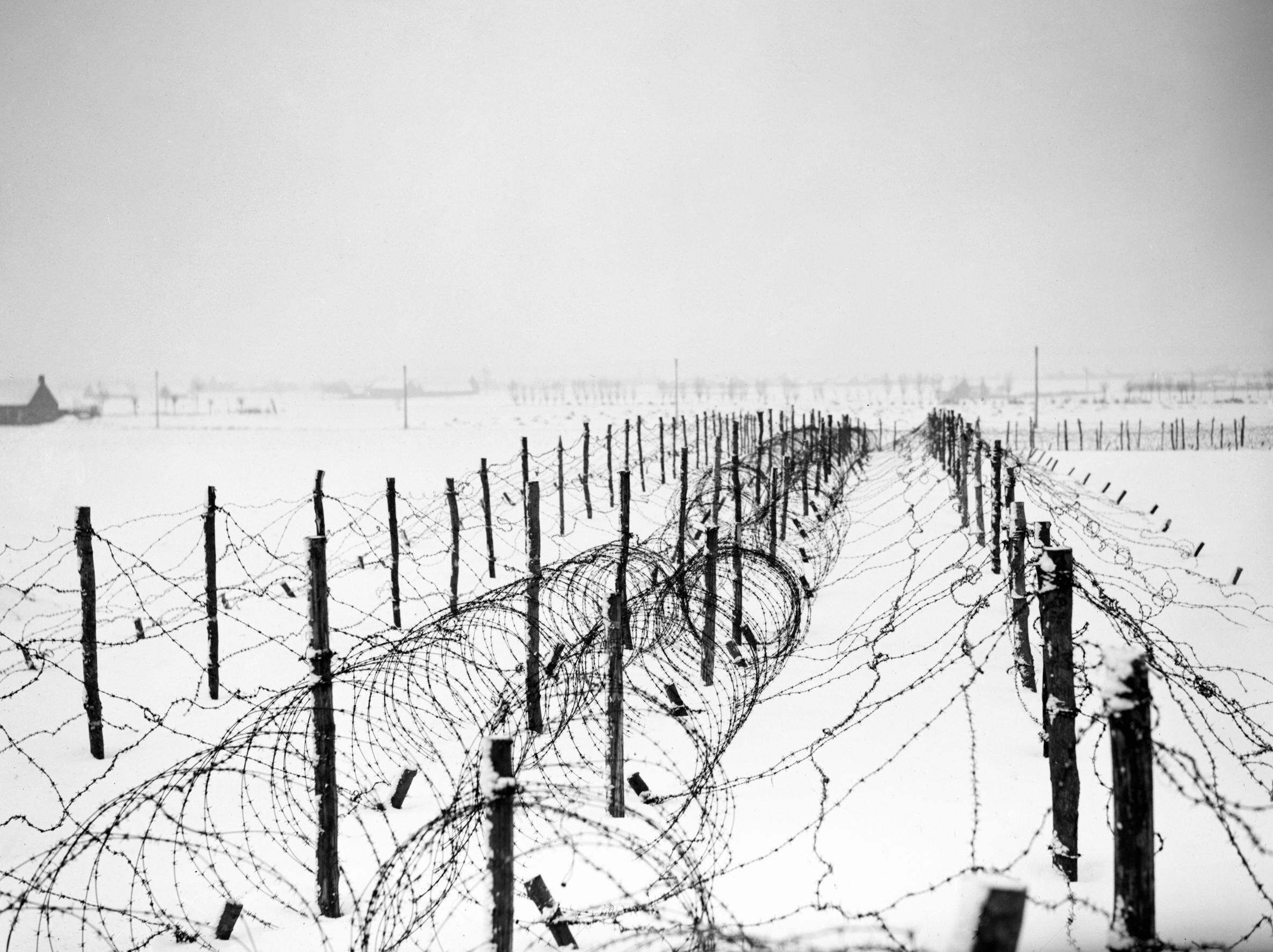 File lines of barbed wire obstacles stretch across snow