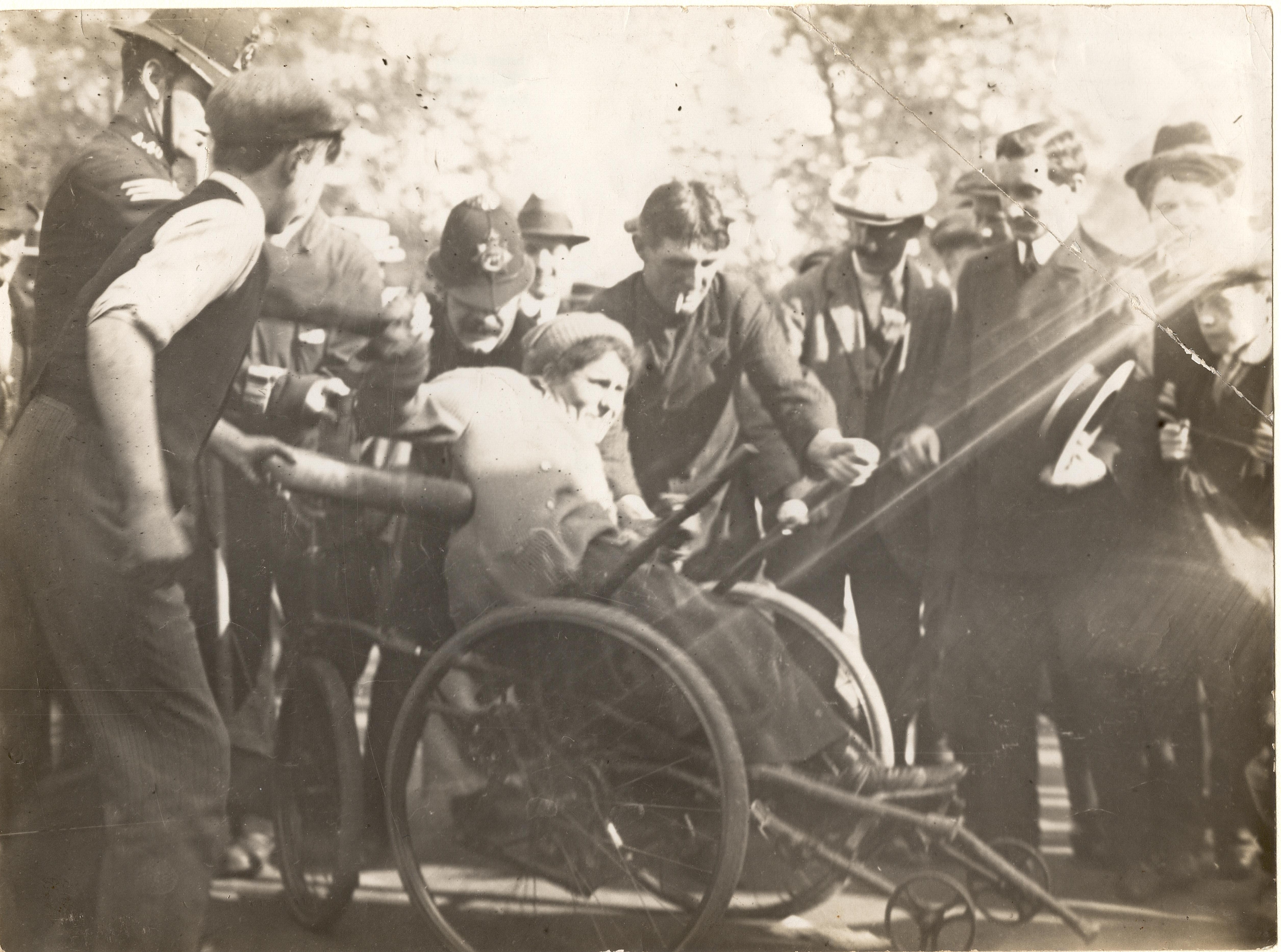 woman seated in wheelchair surrounded by a group of men
