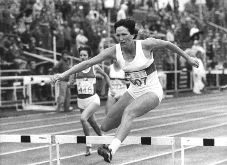 Black-and-white photograph of two women going over hurdles