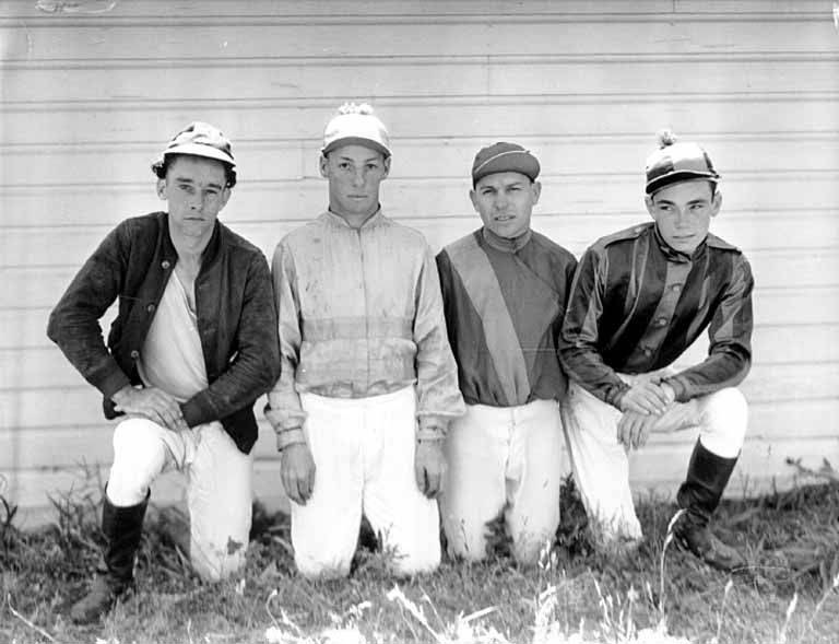 Four_jockeys_kneeling_in_the_grass_in_front_of_a_stable%2C_Washington_State_%284951163393%29.jpg
