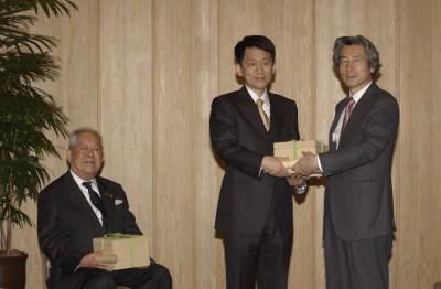 2003年2月7日、総理大臣官邸にて島津製作所フェロー田中耕一(中央)と共に内閣総理大臣小泉純一郎(右)から内閣総理大臣感謝状を受領 Wikipediaより