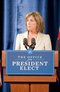 "A pale-skinned woman in her fifties with straight, light brown hair parted near the middle and falling to above the shoulders, wearing a light beige suit jacket, listening with a serious expression to an unseen question as she stands behind a brown podium with a blue and white sign saying ""Office of the President Elect"" and two black microphones, against a blue drapes background."