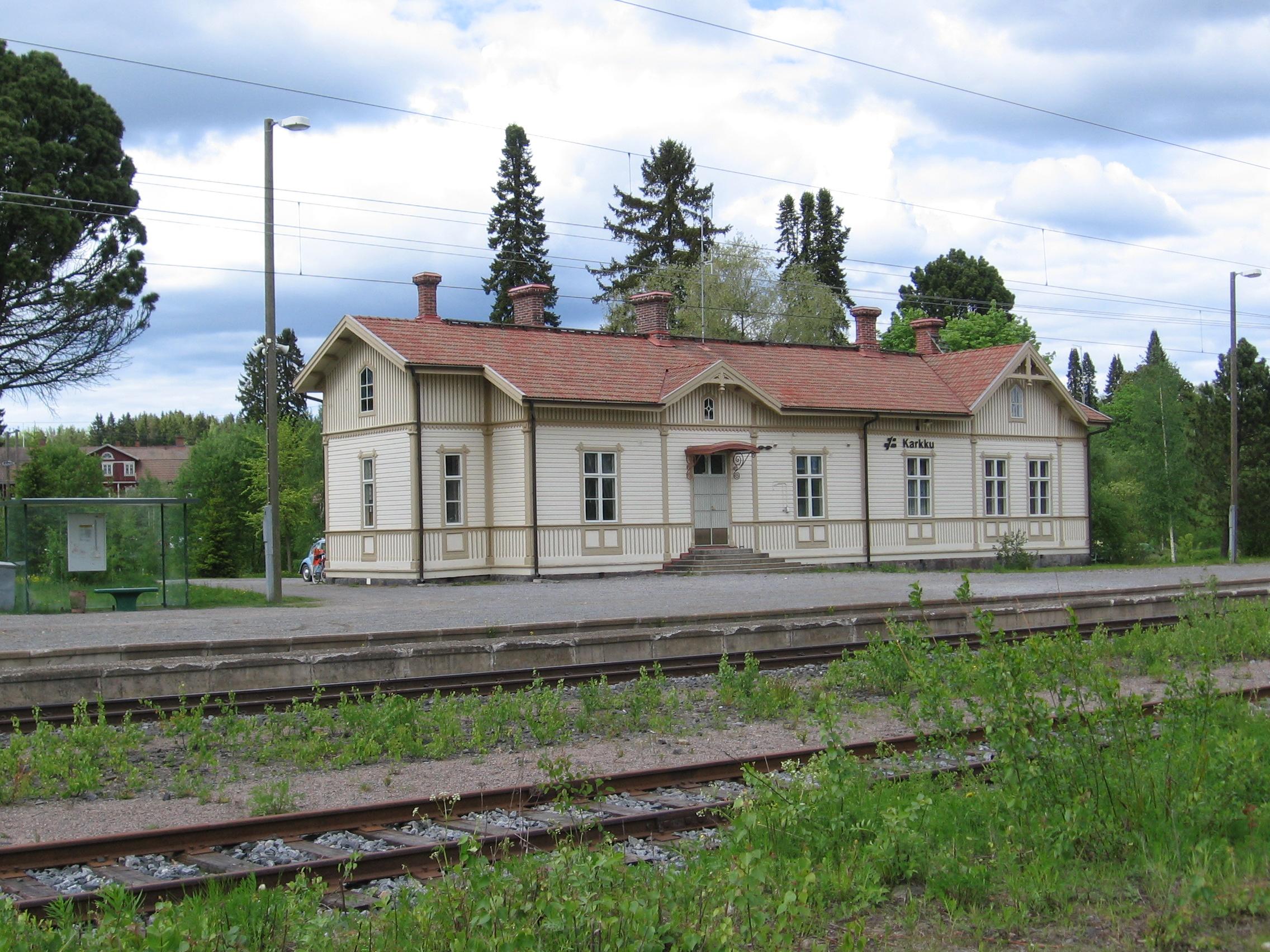 Kesäisessä kuvassa on puinen, melkein maantien vaalean ruskea, yksikerroksinen asemarakennus, jossa on punainen katto. Rakennuksessa on katolla useampi savupiippu. Rakennuksen keskellä on ovi jonka yläpuolella on pieni katos. Oven edessä ovat puiset portaat. Oven oikealla puolella on neljä isoa ikkunaa, joissa kussakin on neljä ruutua. Vasemmalla puolella on yksi iso ikkuna, jonka jälkeen talossa on sisäänpäin nurkka, jossa on ikkuna radalle päin. Talon päädyssä on iso ikkuna ja vintin ikkuna. Pihassa on asfaltti. Talon ympärillä näkyy erialisia isoja puita. Junarata menee kuvan etuosassa kello 8 suunnasta kello 2.30 suuntaan. Kiskoja on kolme paria. Kiskojen välissä kasvaa heinää.