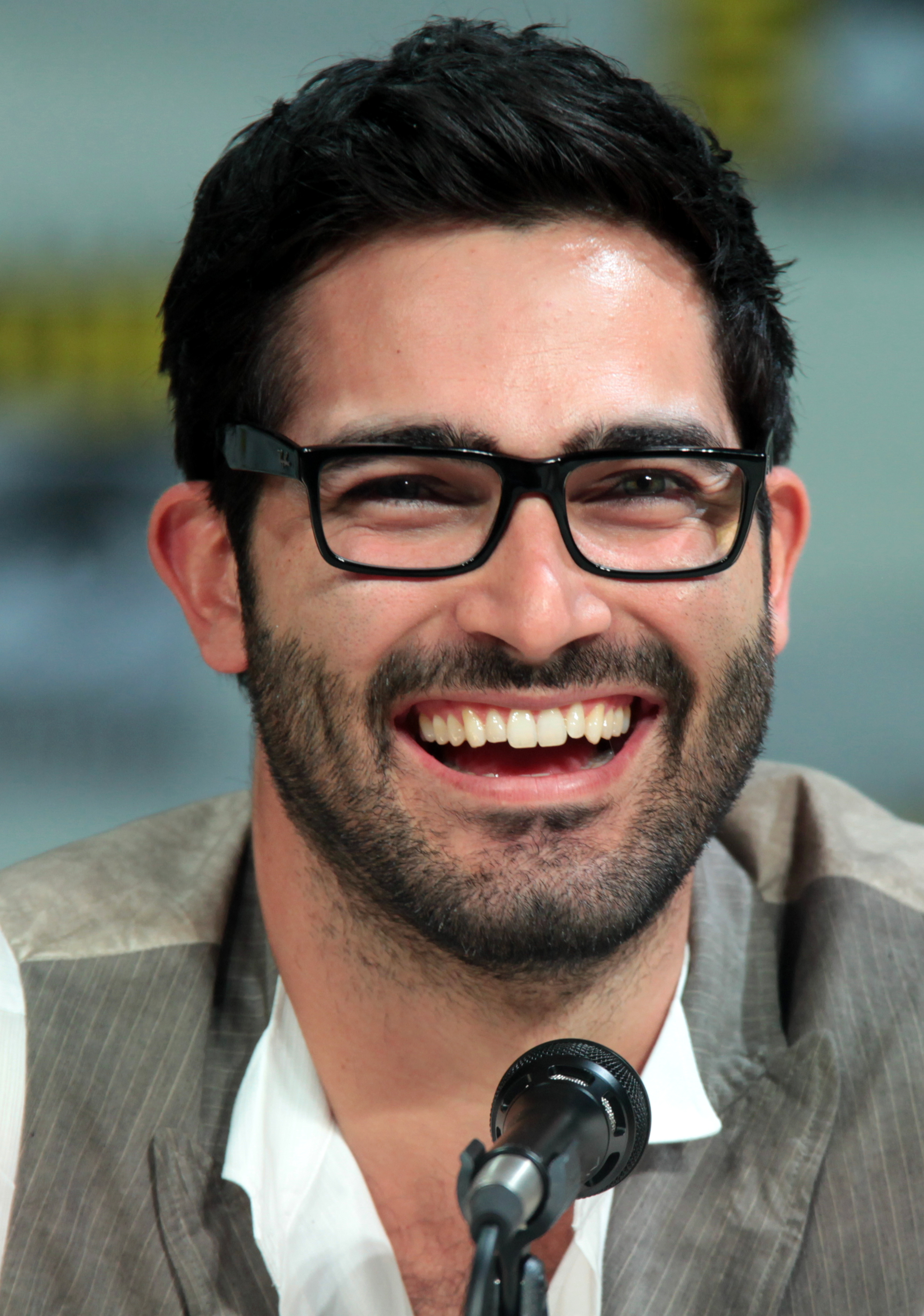 Tyler Hoechlin with glasses talking into a microphone