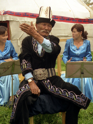 A traditional Kyrgyz manaschi performing part of the Epic of Manas at a yurt camp in Karakol Kyrgyz Manaschi, Karakol.jpg