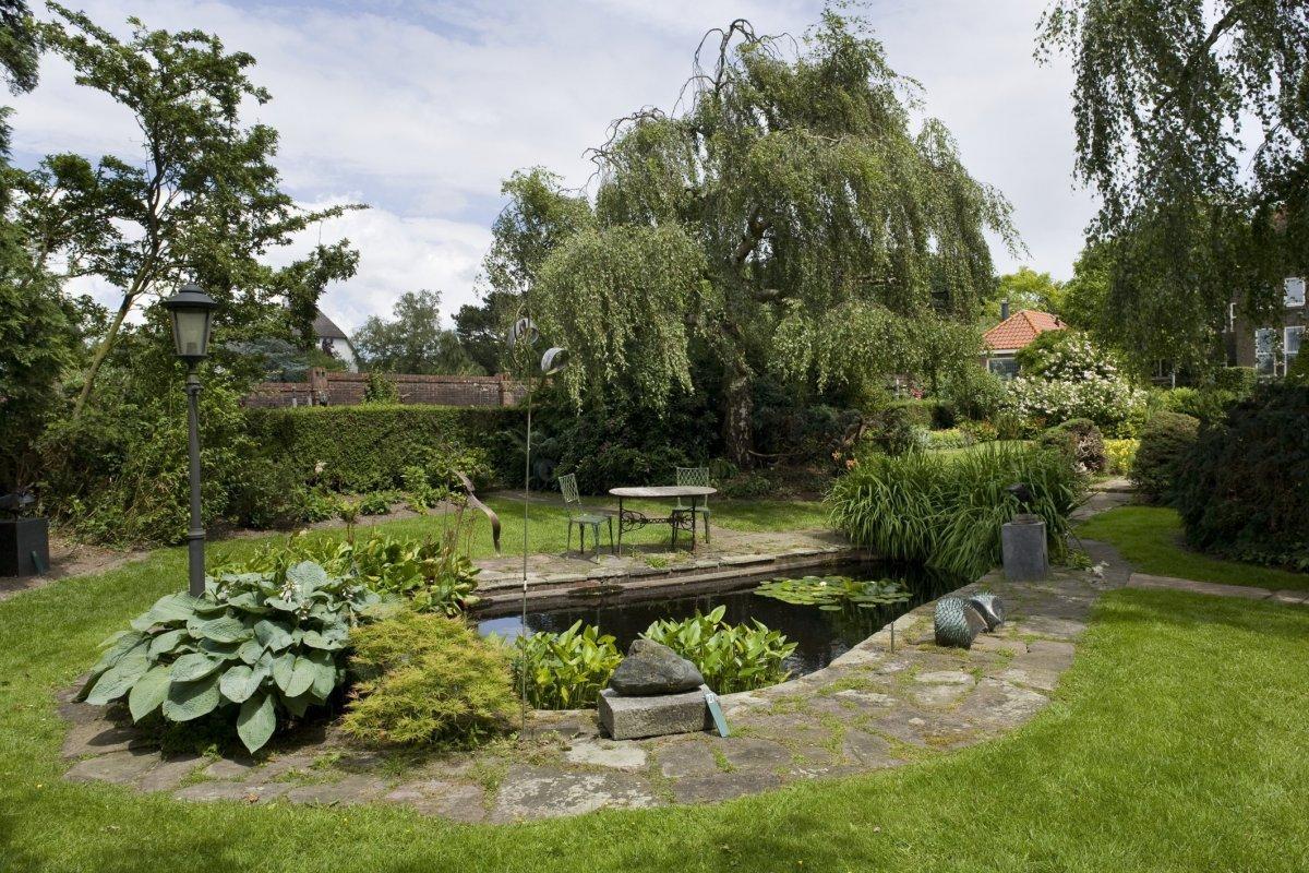 Bestand overzicht tuin met niervormige vijver haren for Een vijver