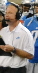 Linehan wearing a white Detroit Lions polo shirt and a headset and holding a clipboard on the Lions sideline