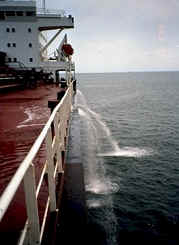 A cargo ship pumps ballast water over the side