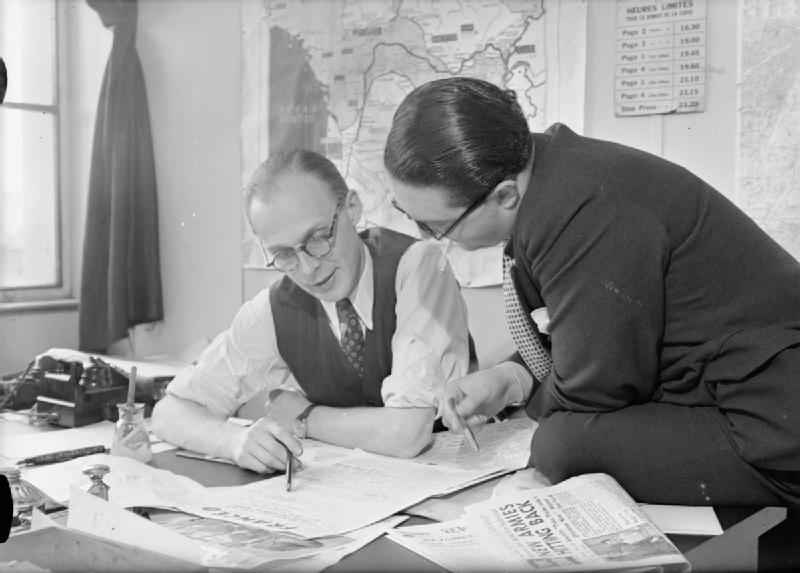 black and white photo of two men reading newspapers