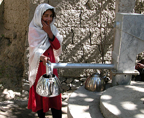 A young girl from Afghanistan gets water from a new hand-pumped well.