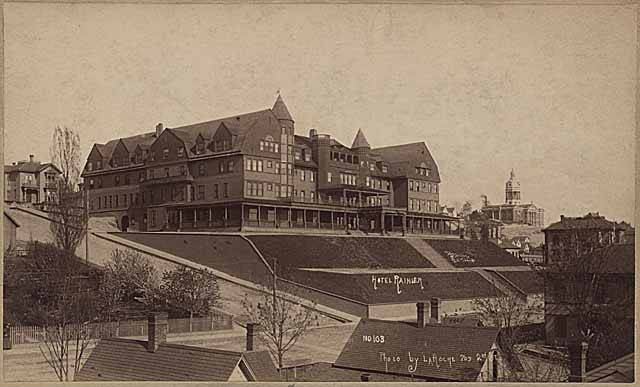 The Rainier Hotel sits atop a hill with stairs leading down to Fourth Avenue. It has two turrets and large bulk.