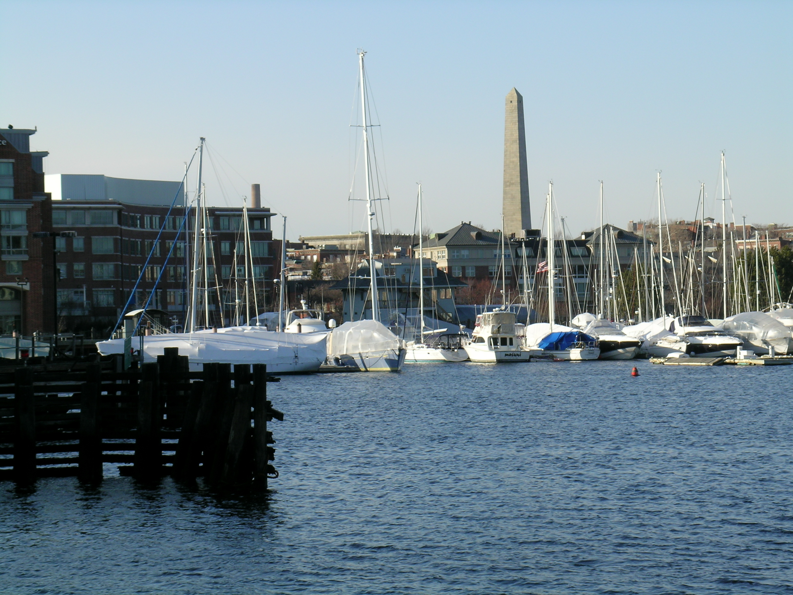 Sailboats moored on the Charlestown side of the Charles River with Bunker Hill Monument in the distance