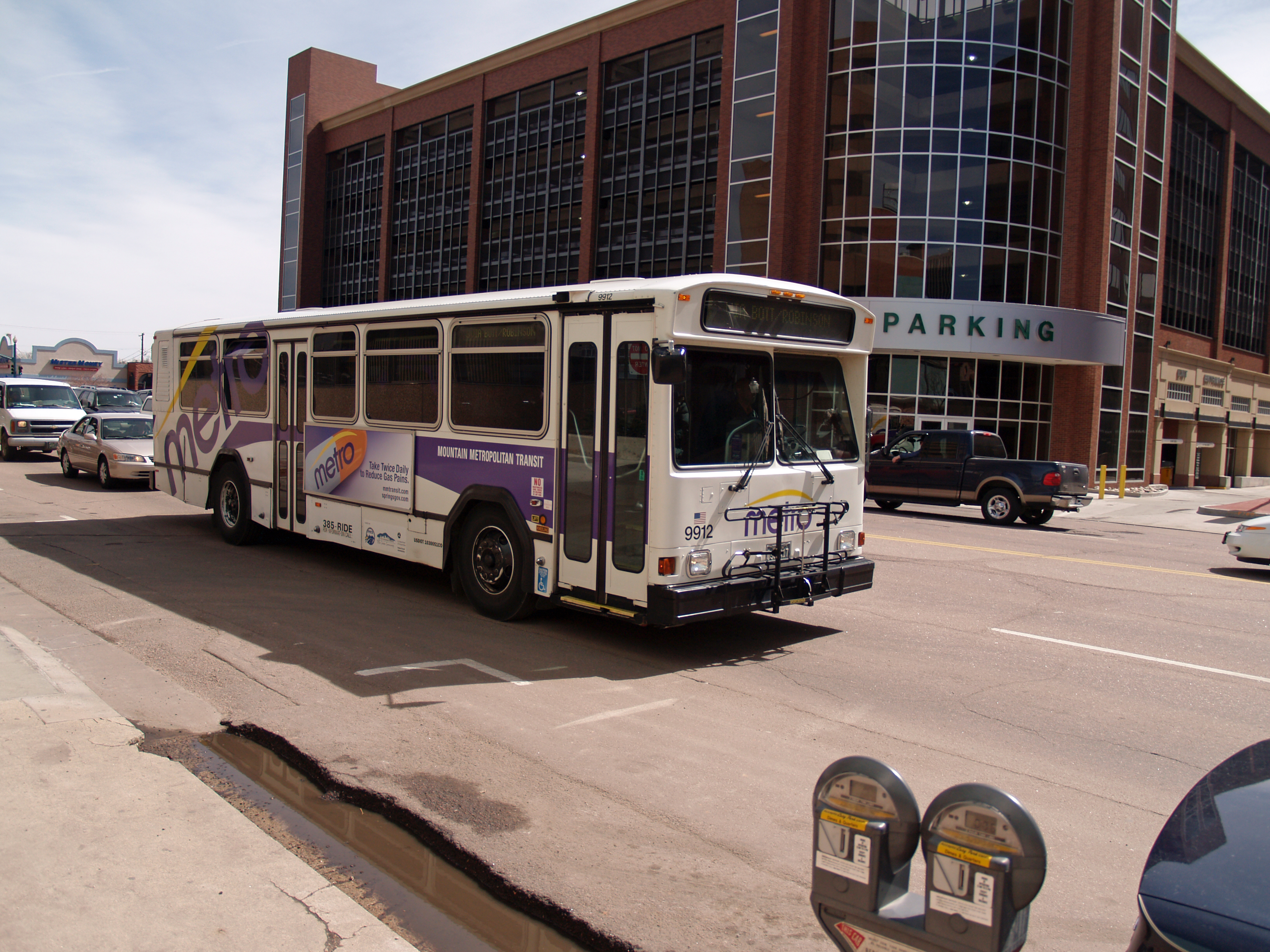 A Metro bus drives past a parking garage in downtown Colorado Springs.