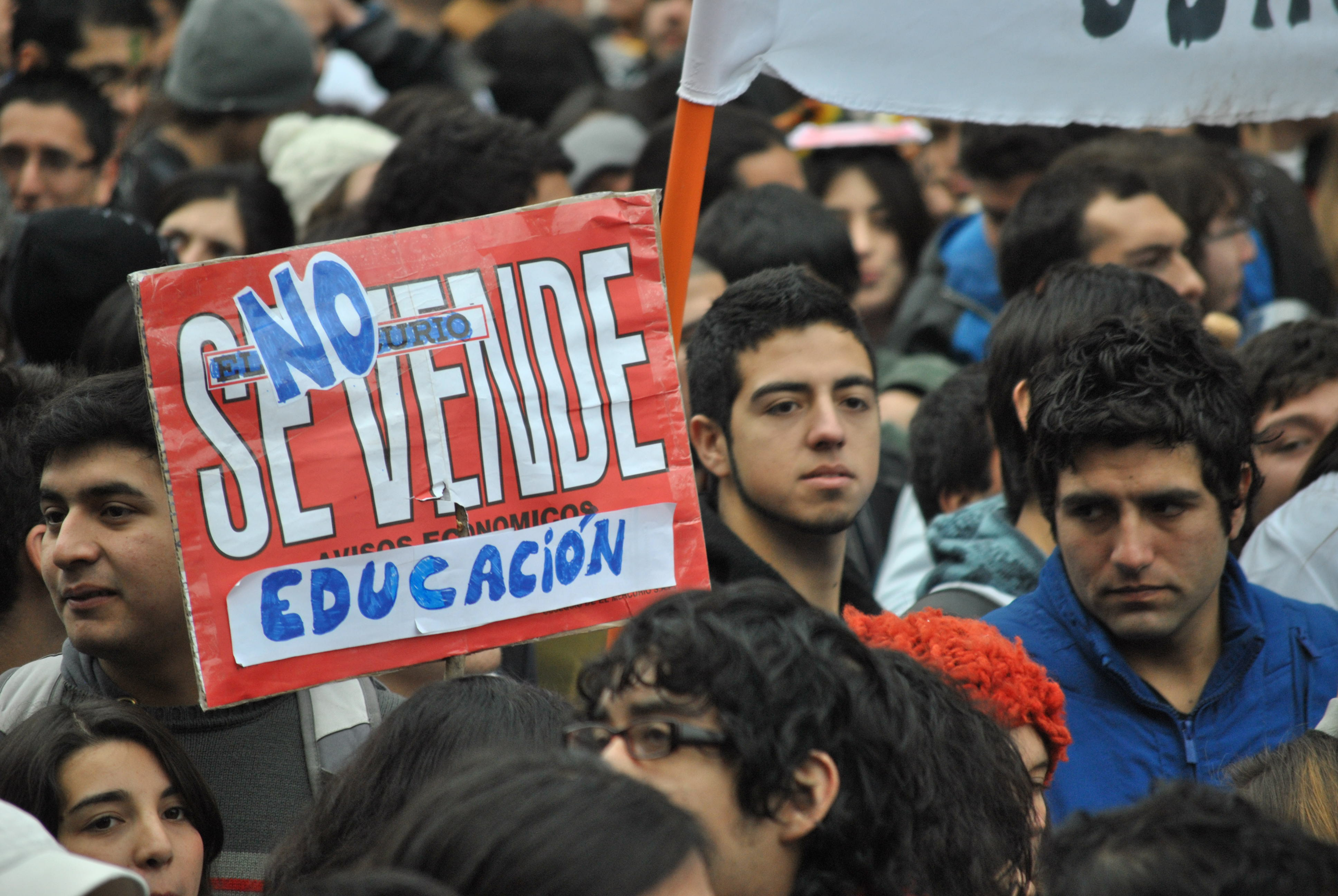 Chilean students with sign, saying Education is not for sale