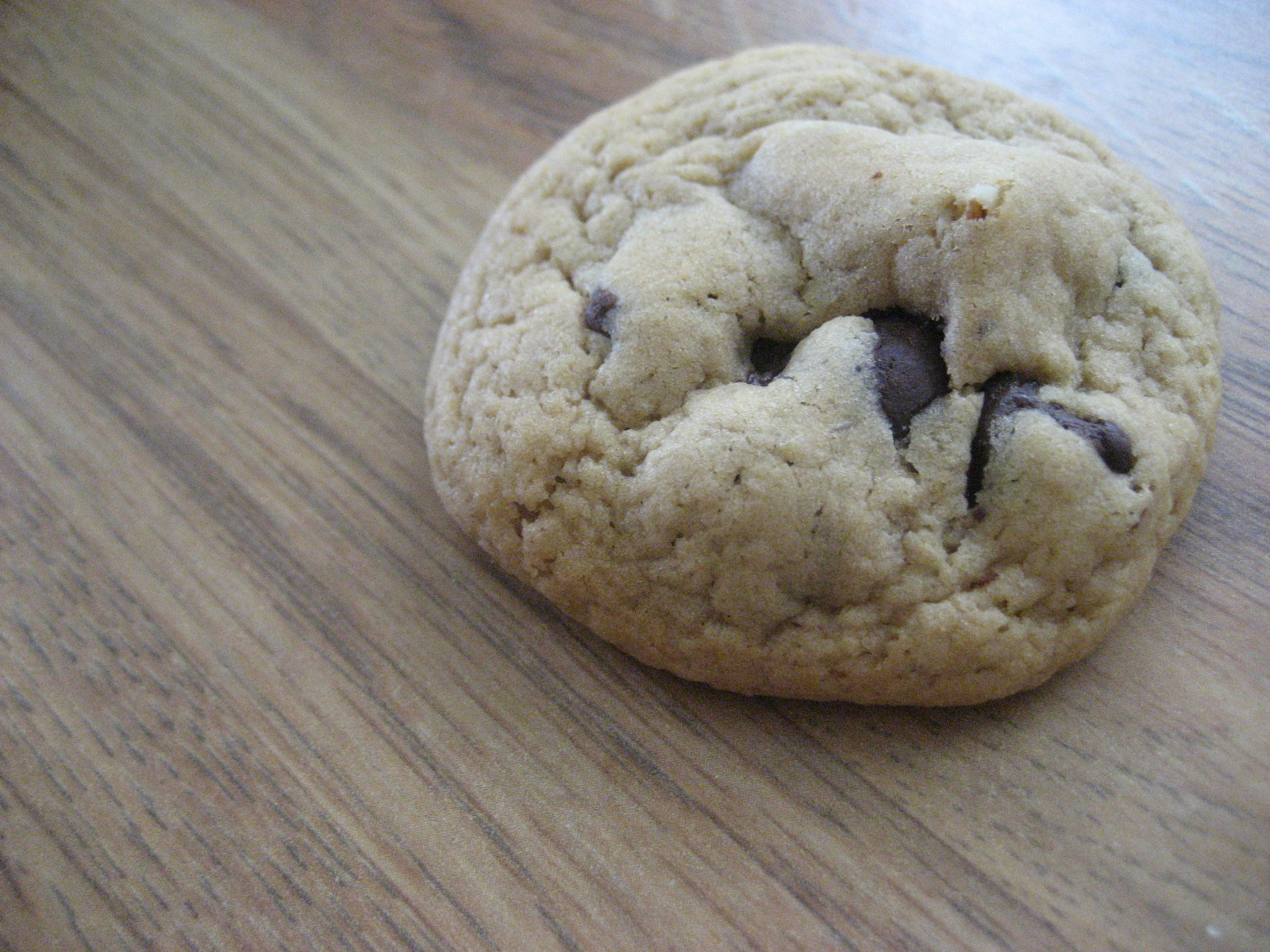 Loner chocolate chip cookie on wood-grain surface.
