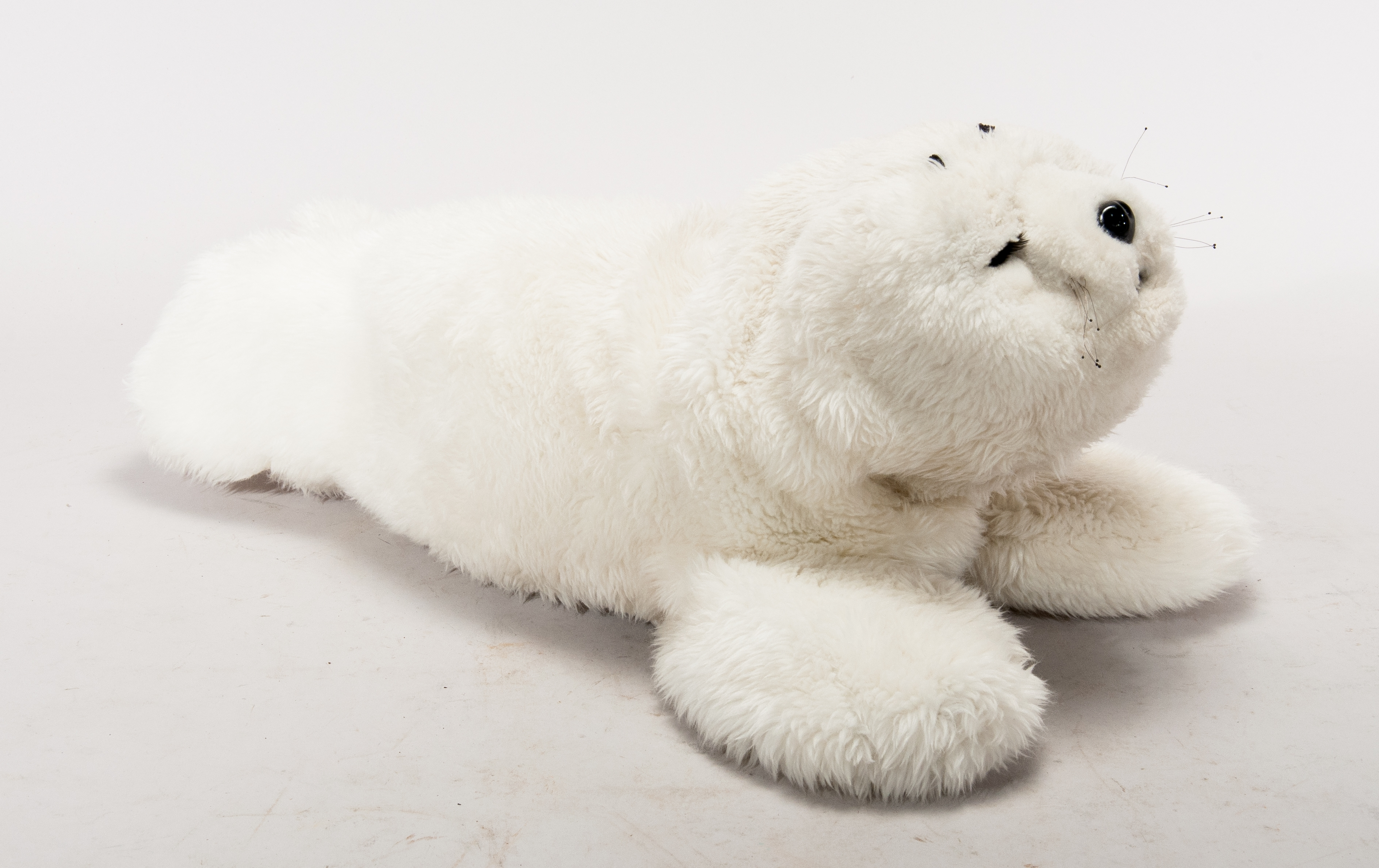 Paro robot, which resembles a plush seal toy. The seal is white and fluffy.