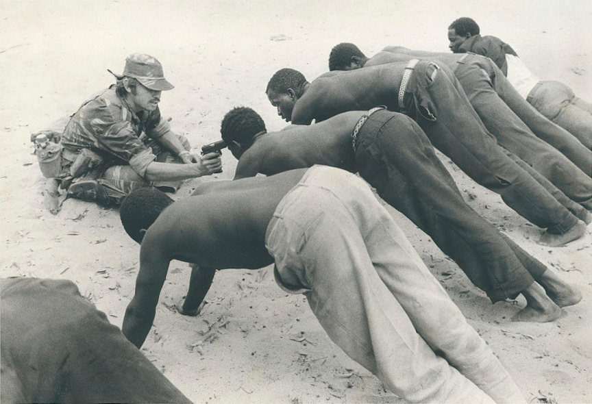 A Rhodesian soldier interrogates villagers in late 1977 at gunpoint. This photograph would become one of the most enduring images of the bush war. Scoutwithgun.jpg