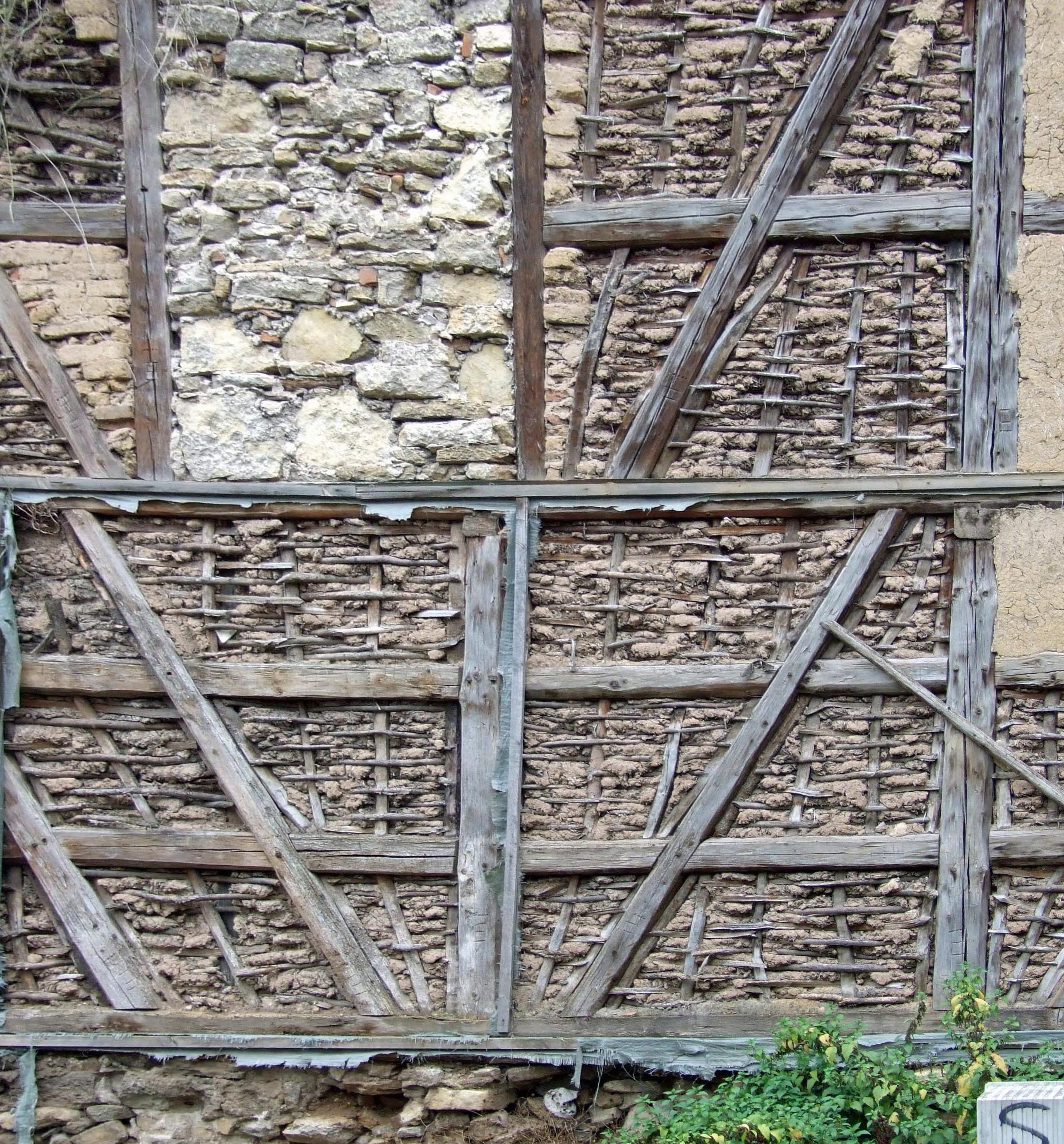 Freigelegte Konstruktion mit Gefachen mit Holzgeflecht und Lehmbewurf sowie Gefachen mit Steinen