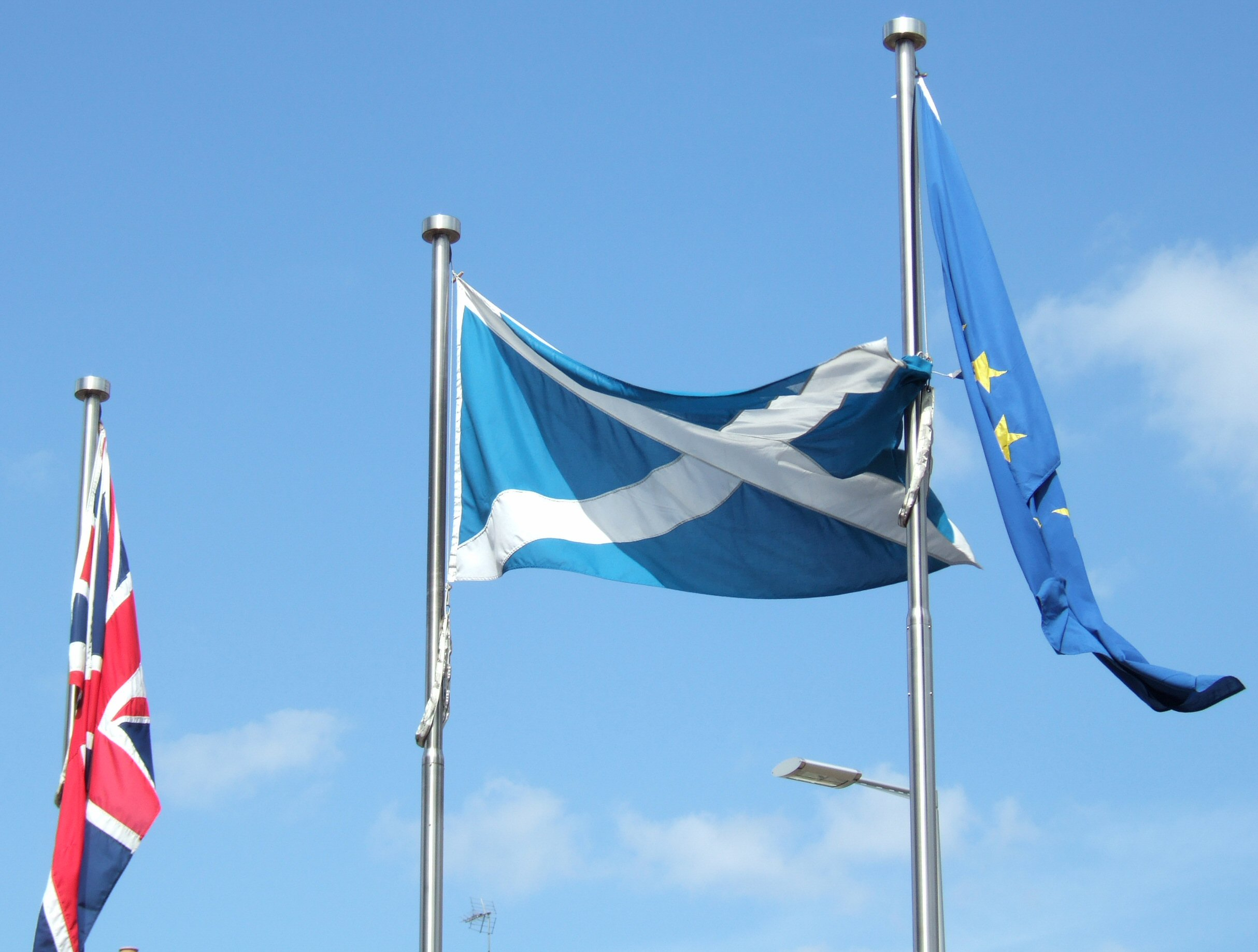 The Union Flag, Flag of Scotland, and Flag of the European Union flying outside the Parliament.