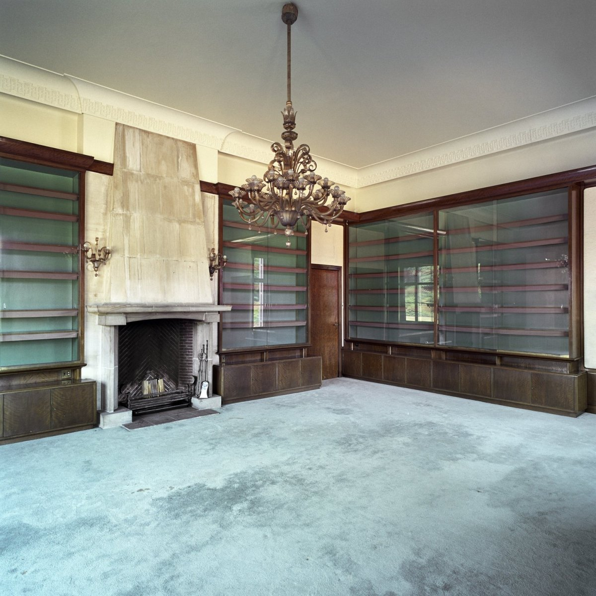 File interieur overzicht van de lege bibliotheek annex woonkamer met kroonluchter en schouw - Whirlpool van het interieur ...