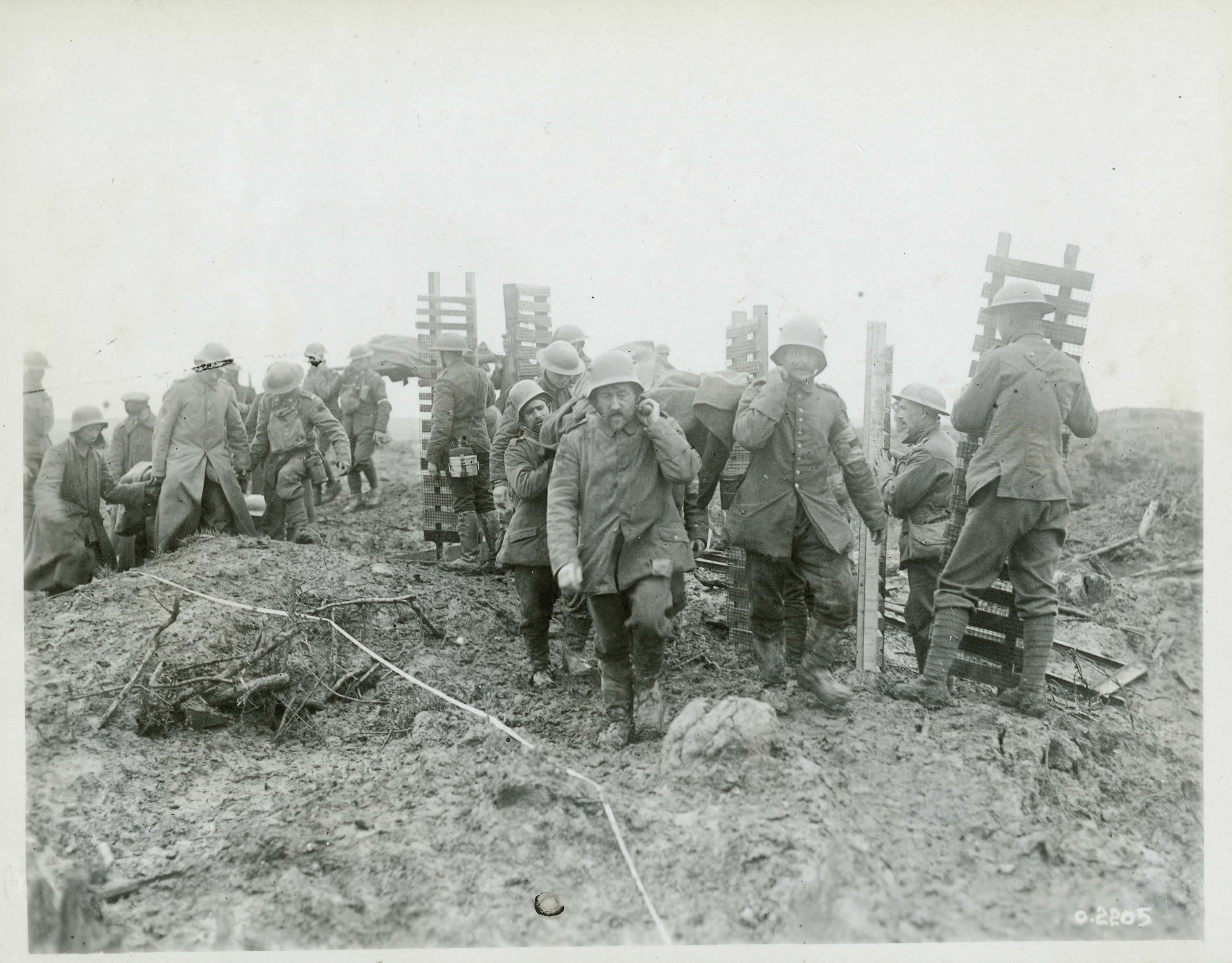 """German prisoners help to carry wounded Canadians away from the front, while Canadians bring forward duckboards or """"trench mats,"""" made of wood overlaid with wire mesh"""
