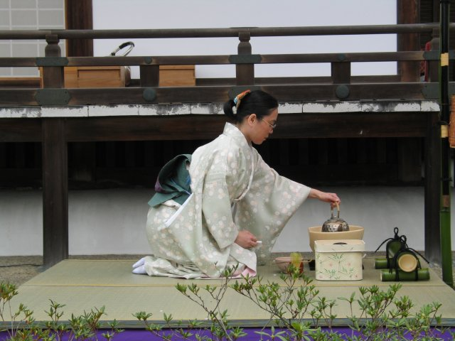 A woman wearing a kimono performs a tea ceremony outdoors, while seated in seiza position.