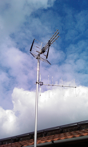 Two Yagi-Uda antennas on a single mast. The top one includes a corner reflector and three stacked Yagis fed in phase in order to increase gain in the horizontal direction (by cancelling power radiated toward the ground or sky). The lower antenna is oriented for vertical polarization, with a much lower resonant frequency. Yagi uda antenna.jpg
