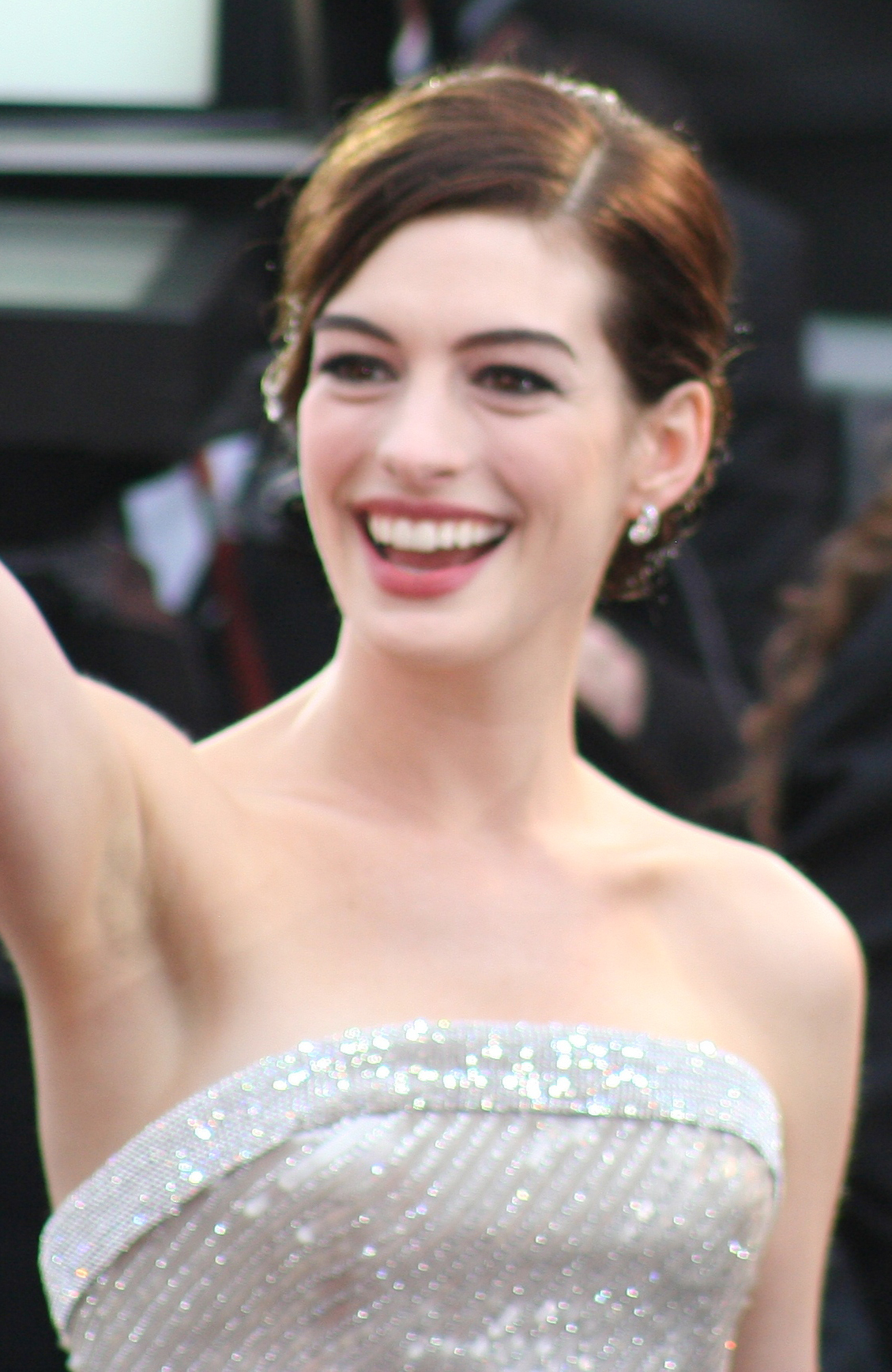 A broadly smiling young woman, wearing a white lame strapless gown and small earrings, waves presumably at a crowd. Her is parted on the left side and pulled up and back, off of her bare shoulders. The background is out of focus and unclear.
