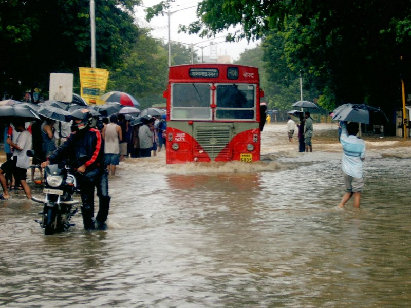 A flooded street in Mumbai with a BEST bus on it.