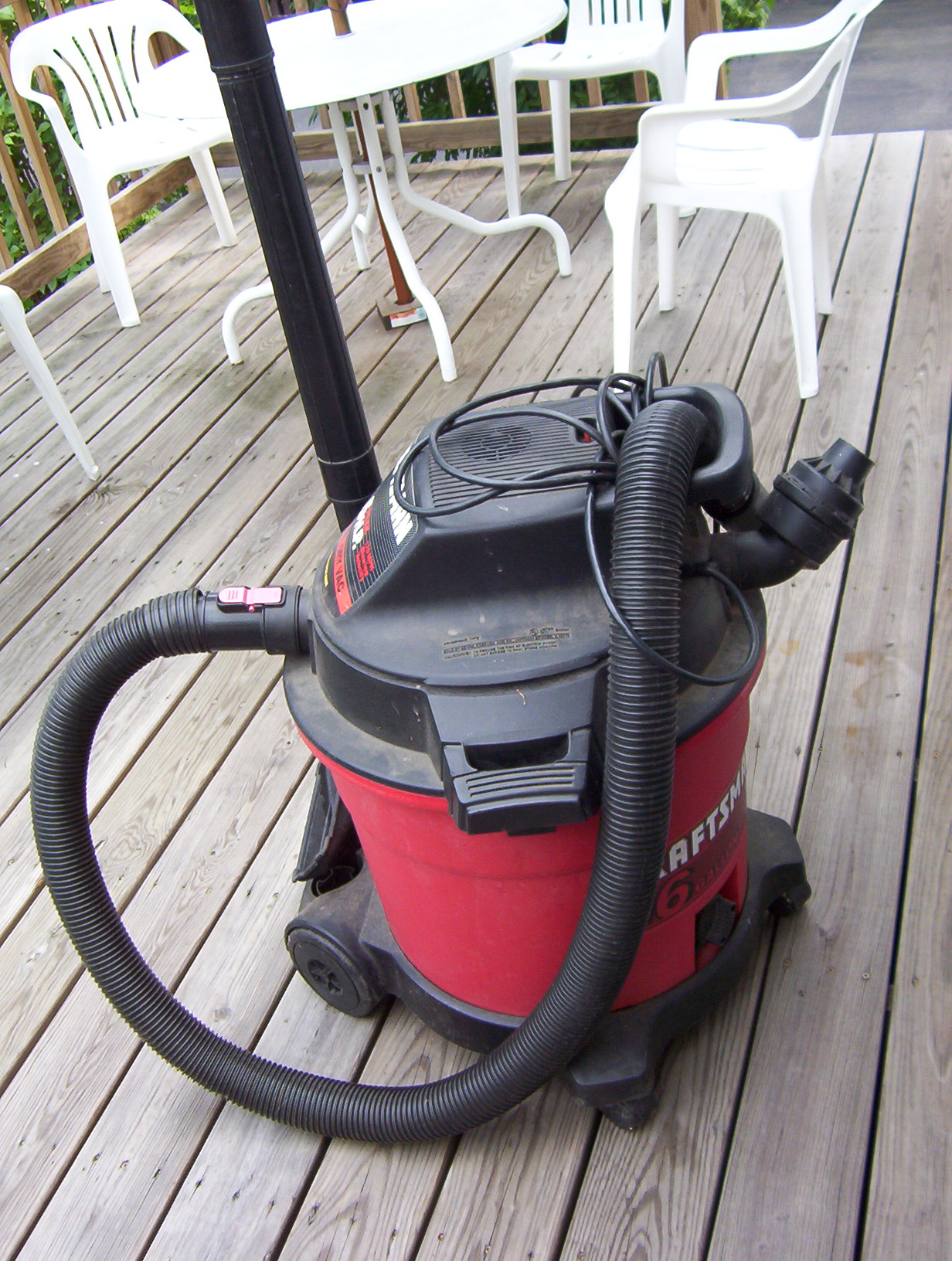 a carpet cleaning macine on a wooden deck with white chairs and table in the backgound