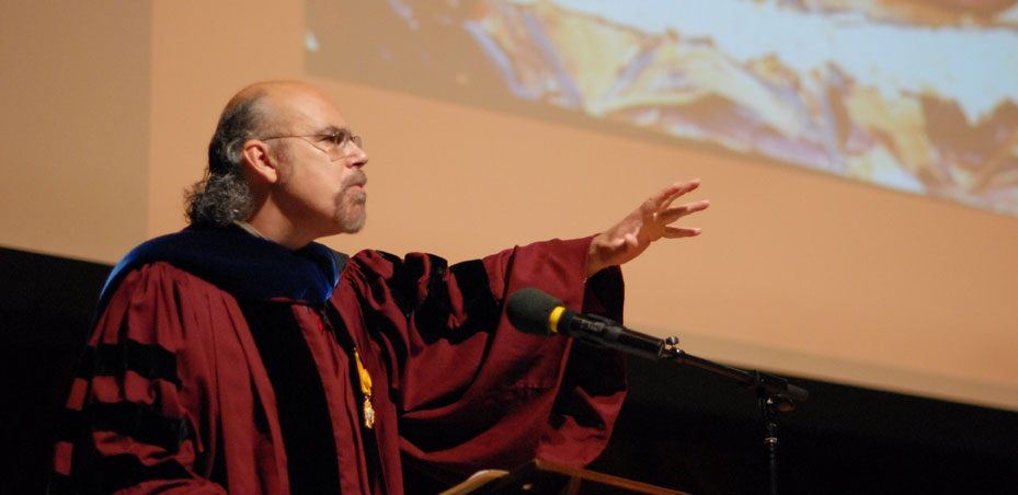 """David Carrasco delivers the Harvard Divinity School Convocation Address in front of an image of """"Boxcar"""" by George Yepes."""