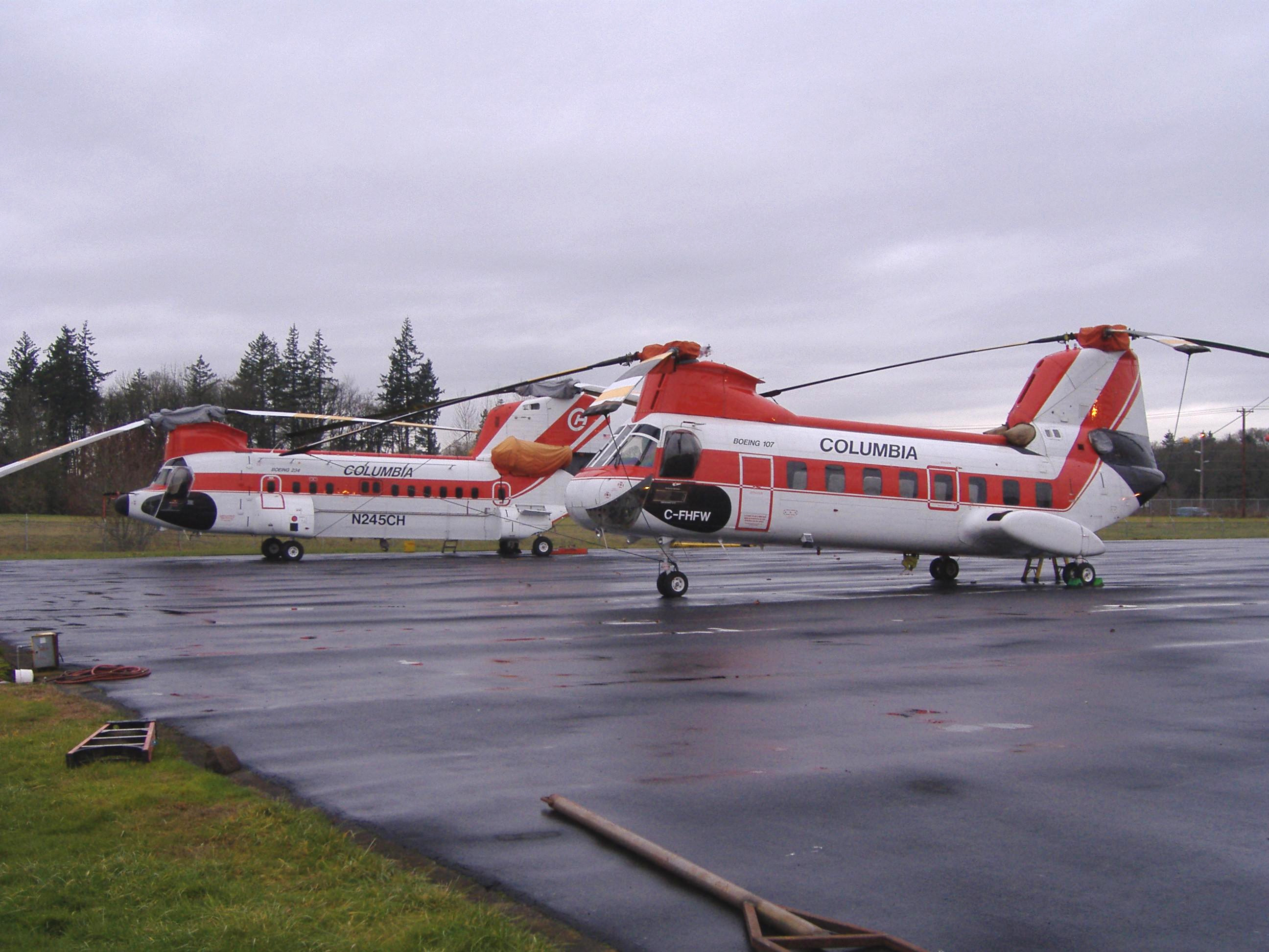 Columbia Helicopters Inc Boeing Vertol 107 C-FHFW and Boeing 234 N245CH rest on the company pad in Aurora, Oregon.