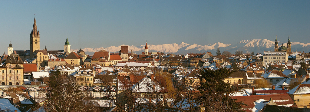 Sibiu Skyline from left to right Council Tower, Evengelical Lutheran Church, Catholic Church, Reformed (Calvinist) Church, Orthodox Church and in the background the highest peak Negoiu.