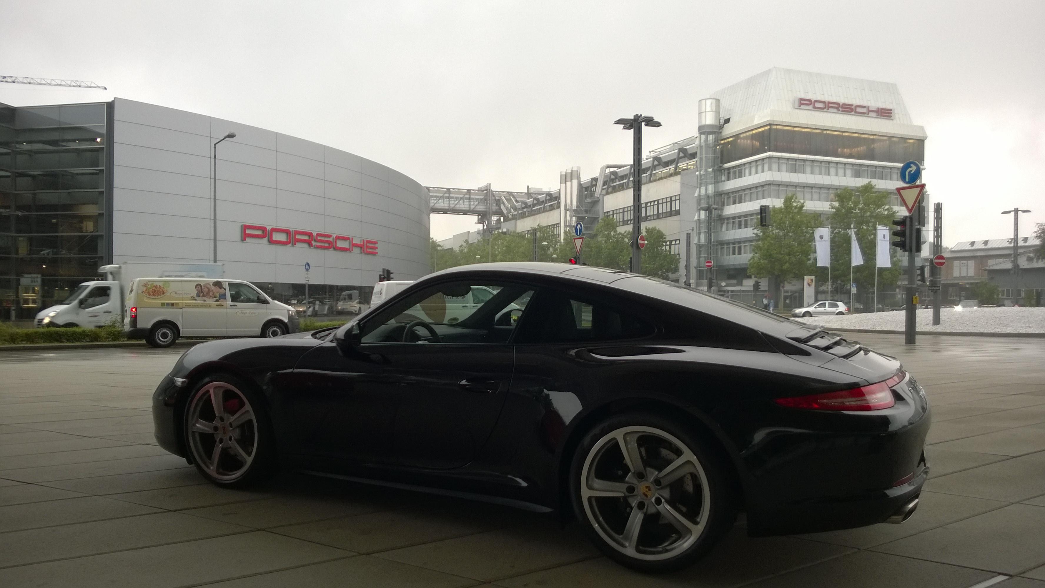 A 911 before the factory in which it was assembled, Porschewerk Stuttgart (right), and the manufacturer's central dealership, Porsche Zentrum Stuttgart (left).