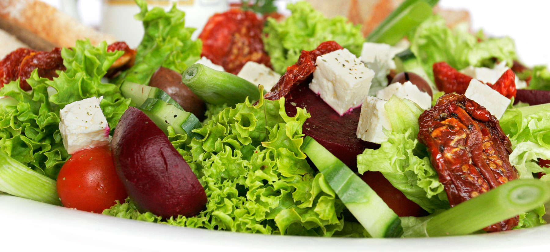 Assorted salad vegetables in a platter, against a white background